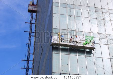 The gondola lift or scaffold for glass cleaner with the worker on the building construction site