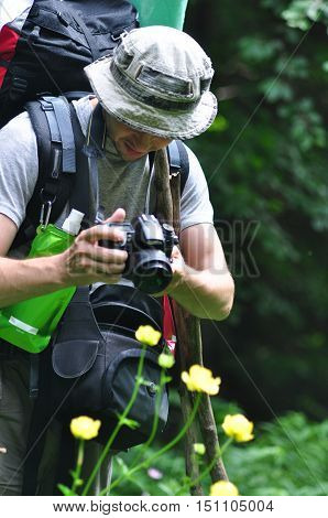 Nature photographer making photo of beautiful nature. Man traveler taking a picture of landscape. Man explorer adventure travel outdoor.