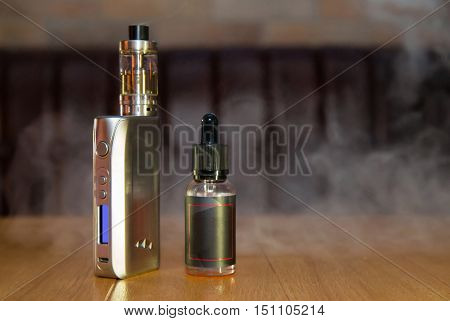 Electronic mod and vial on a table. White smoke in the background.