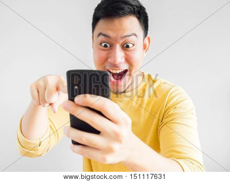 Asian man is playing mobile game on smartphone.