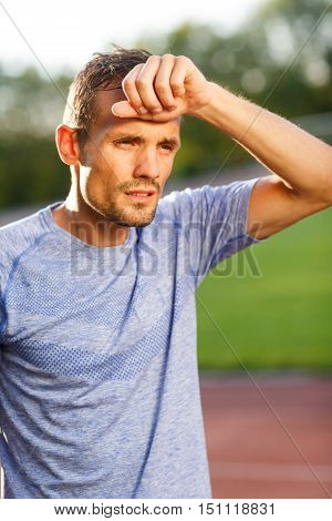Man in light blue t-shirt wiping sweat after running. Vertical image on nature background