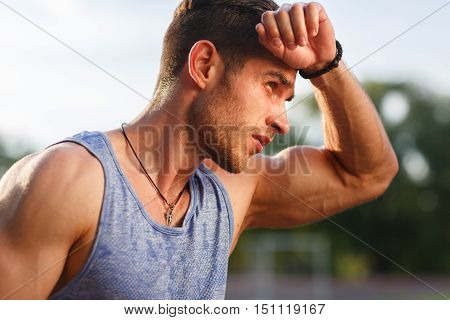 Portrait of fatigued fitness guy after exercises on hot sunny day