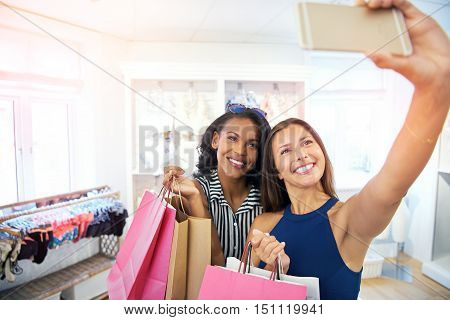 Two young women taking a selfie in a fashion boutique as they shop together for clothes posing for the camera on their mobile while holding their purchases in colorful bags