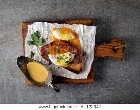 Poached with bacon and toast, parsley and spices on paper on a cutting board on a gray background