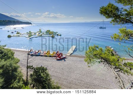 BOL, ISLAND BRAC, CROATIA - JULY 17, 2016: Zlatni rat beach in the morning waiting for swimmers, surfers and boats in high season