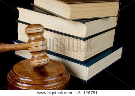 Wood gavel soundblock and stack of thick old books on a black background