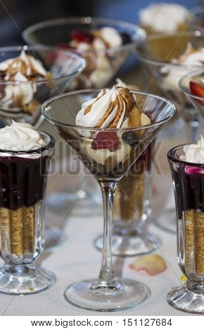 Delicious array of wedding desserts on a buffet table with fruity meringues and parfaits in elegant glasses