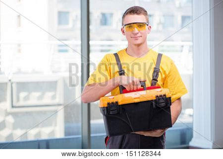 Young construction worker in yellow coveralls
