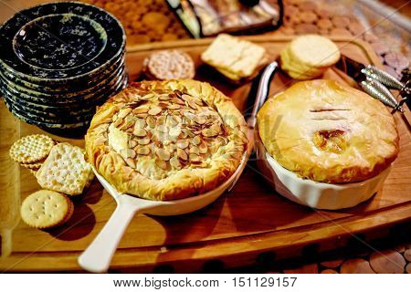 Gourmet baked brie cheese wrapped in filo with almonds and preserves, served as an appetizer in a beautiful table.