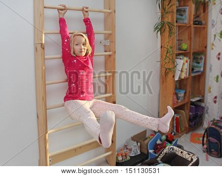 Beautiful athletic girl plays sports on Wall bars in the children's room