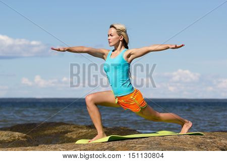 caucasian woman stretching at the seashore during summer training