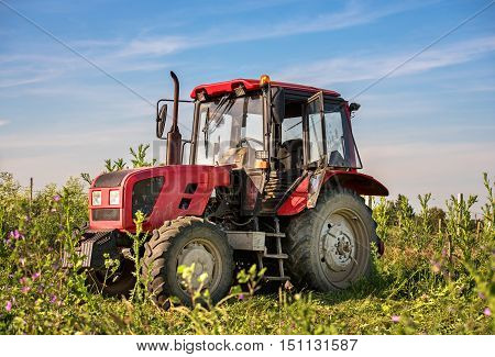 A stationary red tractor is parked on the edge of a field of barley against an overcast sky.