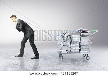 Businessman dragging trolley with heap of book on grey background. Education concept. 3D Rendering