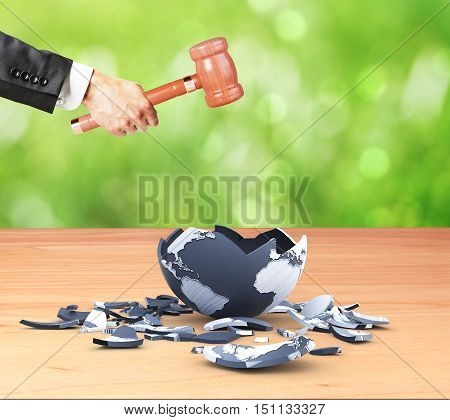 Businessman hand cracking terrestrial globe with wooden hammer on green background. World destruction concept. 3D Rendering