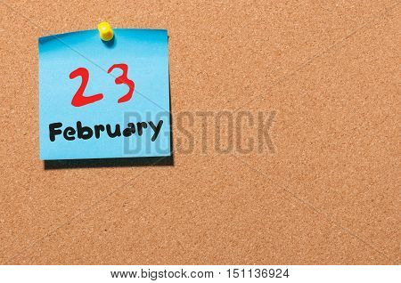 February 23rd. Day 23 of month, calendar on cork notice board background. Winter time. Empty space for text.