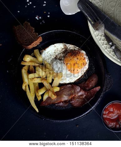 fried eggs with bacon, fried potatoes in a frying pan on a dark background