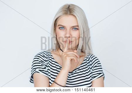 Portrait of beautiful blond woman with finger on lips isolated on grey background. Blue eyes teenage girl keeping a secret