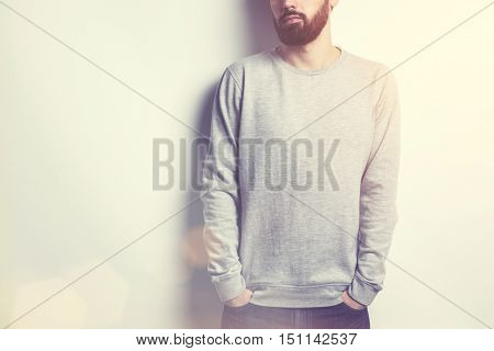 Young man in long sleeved sweatshirt on light grey background on sunny day. Toned image. Mock up