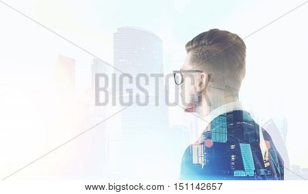 Side view of man in glasses staring at Moscow City panorama. Concept of business climate. Mock up. Double exposure