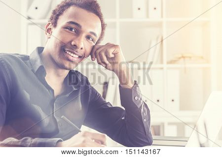 Attractive black businessman working on project on office desk with laptop and notepad. Bookshelf with documents in the background. Toned image