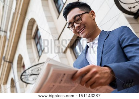 Smiling Asian businessman in glasses is reading a newspaper at the front steps of his house. Concept of businessman's morning