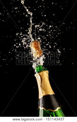 Green champagne bottle with gold foil and cork explosion