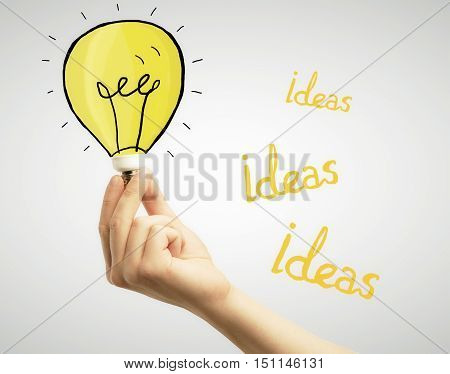Hand holding creative lamp sketch on light background. Ideas concept