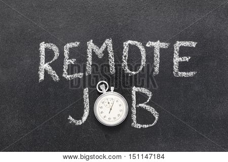 remote job phrase handwritten on chalkboard with vintage precise stopwatch used instead of O
