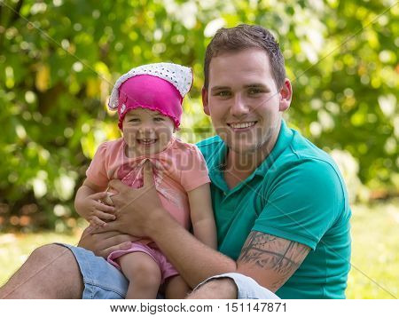 Dad and his little daughter in the park on a summer day