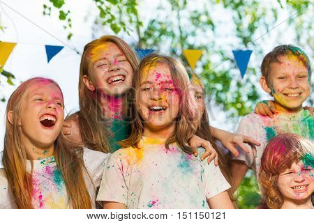 Portrait of happy kids, age-diverse boys and girls, smeared with colored powder