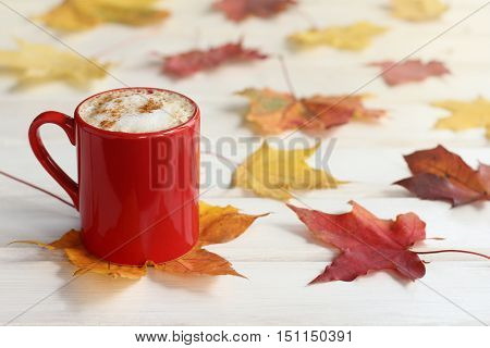 red mug with a frothy cappuccino on the background of fallen leaves on the maple desk / coffee with the aroma of cinnamon and autumn