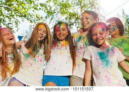 Six kids, smeared with colored powder, standing together during the festival of colors and spring