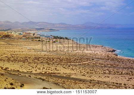 Breathtaking view from above on on of the beast beaches in the world the Beach Sotavento on the Canary Island Fuerteventura Spain with a village and touristic resorts and mountains on the background.