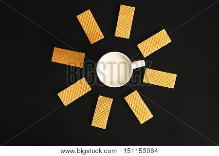 Useful wafer lying in a circle with cup of milk on the black table