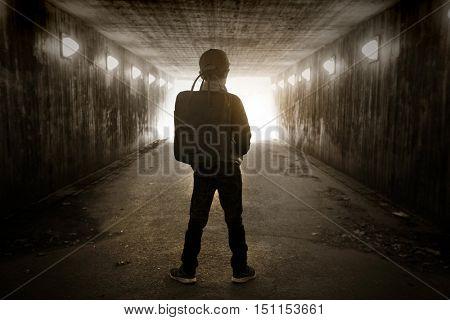 School child walking in a dark subway