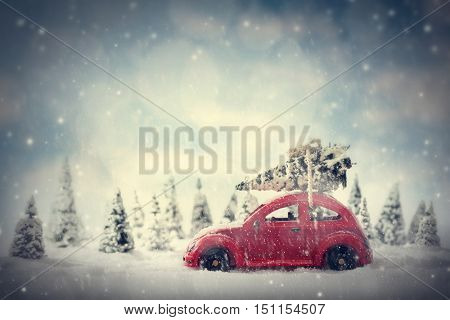 Retro toy car carrying tiny Christmas tree. Fairytale, miniature scenery with snow and forest. Generic brandless wooden car.