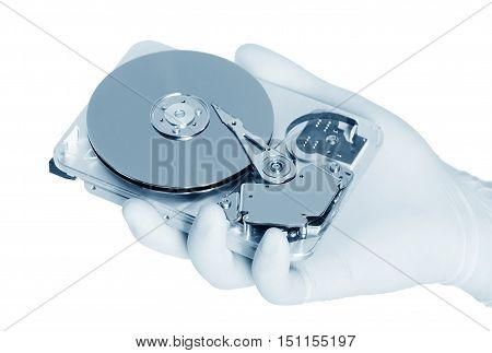 Computer hard disk held by a white gloved hand isolated