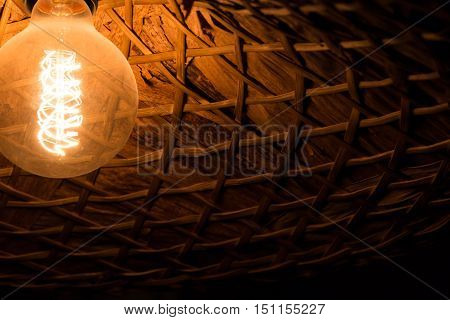 Antique edison style light bulb in a wicker lampshade Vietnamese-style