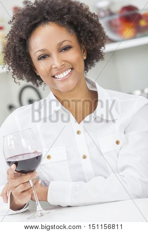A beautiful happy mixed race African American girl or young woman with perfect teeth drinking red wine in her kitchen