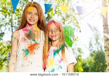 Portrait of two beautiful girls smeared with colored powder on Holi festival
