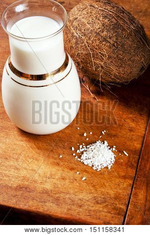 Coco milk, coconut chips and fresh coconut on a wooden table