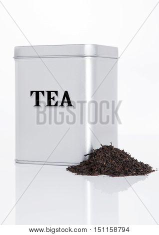 Black tea steel jar with loose tea next to it on white background