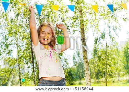 Happy little girl, smeared with colored powder, dancing on Holi color festival