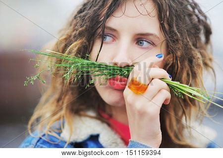Young Funny Girl With Dreadlocks Poses A Grimace, Putting A Tuft Of Grass On The Lips, Outdoors, Clo