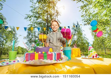 Portrait of happy smiling boy holding birthday gifts, standing next to the birthday cake at the outdoor party