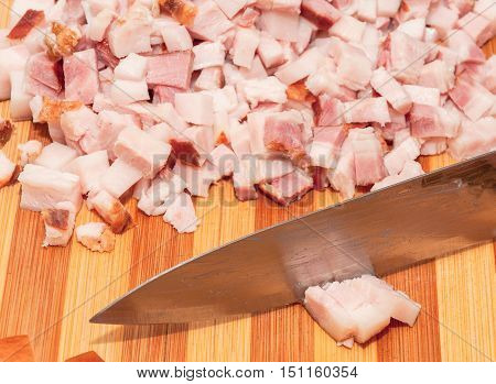 Bacon cut into small pieces and a knife slicing a piece of bacon