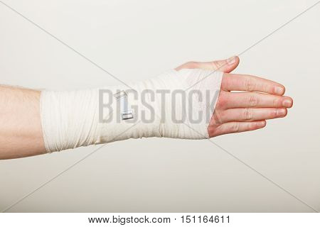 Fractures and dislocations concept. Male hand in white bandage. Helpful medication for painful palm arm of young man.
