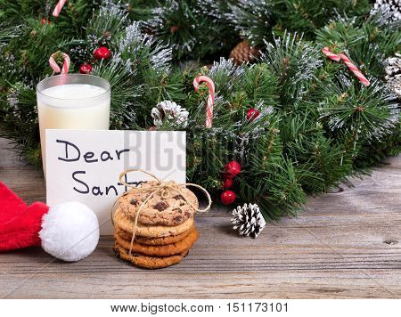 Stack of cookies a glass of milk and letter for Santa with evergreen decoration in background.