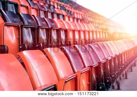 Rows of black and red plastic stadium seats with sunlight