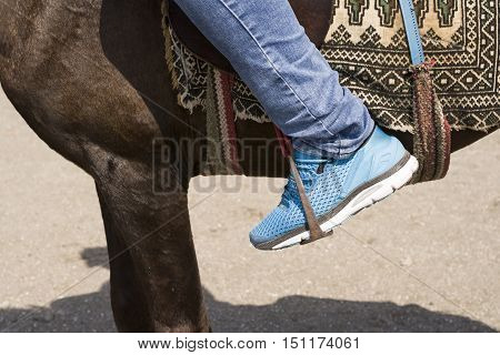 Close up view of Rider Foot on a Horse pedal Blue jean with Sport Shoe
